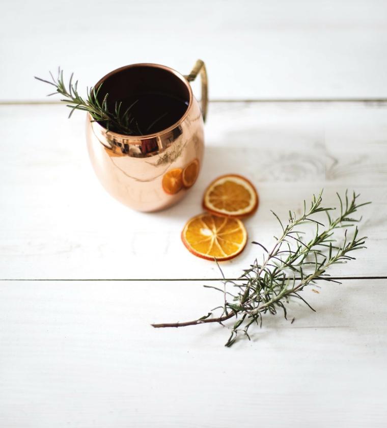Fette di arancia e rametti di rosmarino fresco, decori natalizi, tazza di metallo per profumare l'ambiente