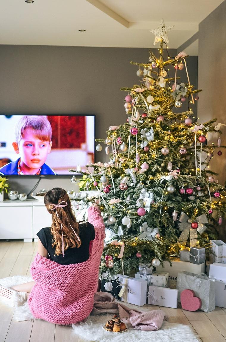 Pacchi regalo sotto l'albero, donna che guarda la televisione, addobbi natalizi fatti a mano