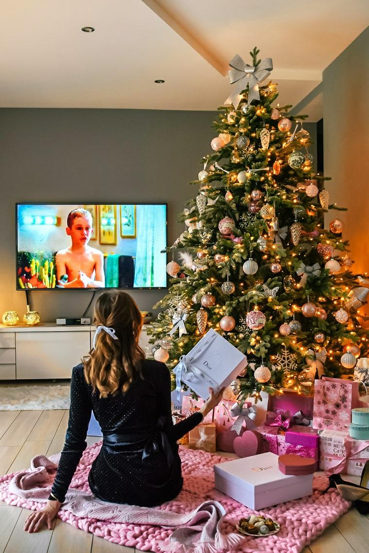 Pacchi regalo sotto l'albero, donna che guarda la tv, decorazioni natalizi fai da te