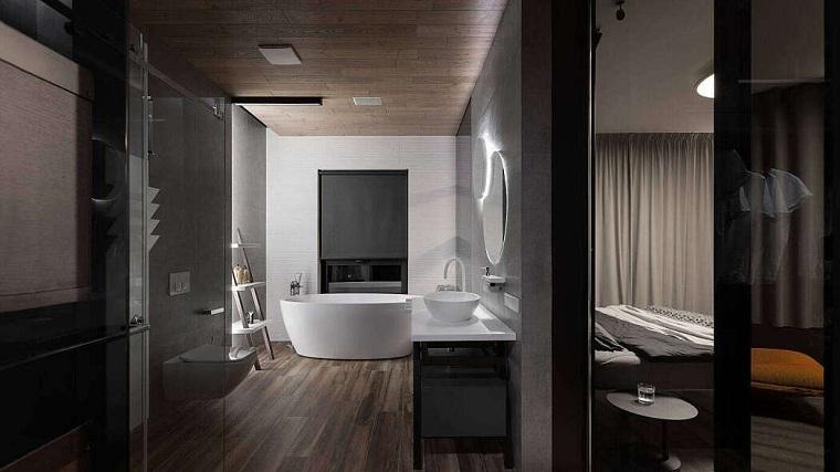 Sala da bagno con vasca ovale, pavimento in legno parquet, mobile con lavabo da appoggio