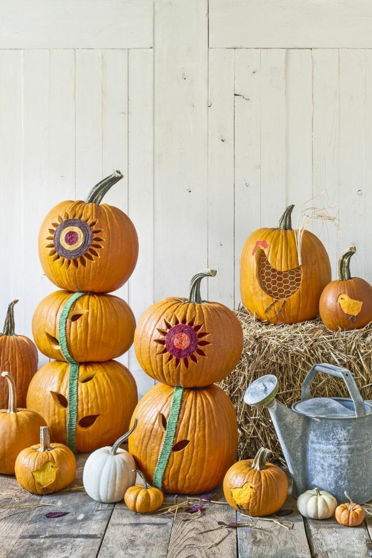 Zucche intagliate, zucche per Halloween, disegni con intagli, balla di fieno
