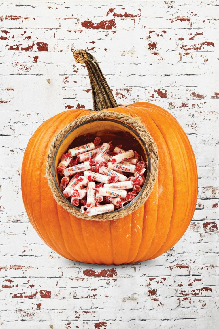 Come intagliare la zucca, zucca con buco, caramelle di Halloween in una zucca, parete di pietra