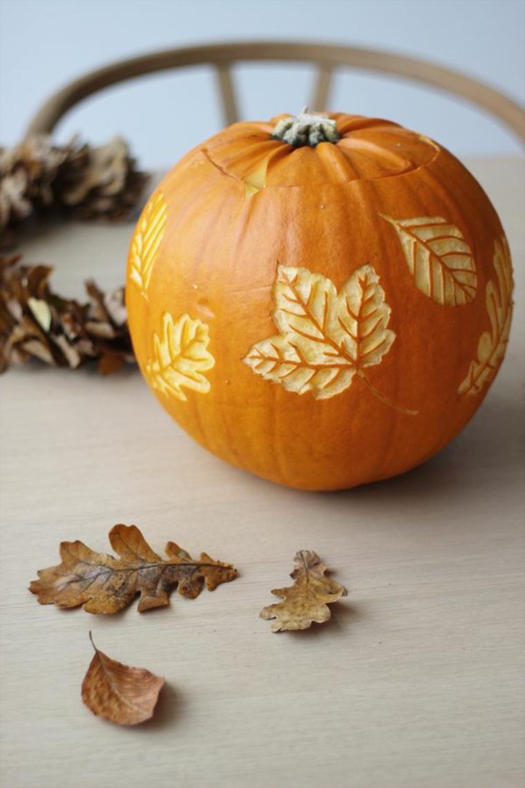 Come intagliare la zucca, zucca con disegni di foglie, foglie secche autunnali