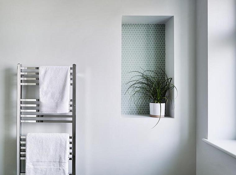 Bagni piccoli con doccia e lavatrice, parete con nicchia rivestita con piastrelle mosaico