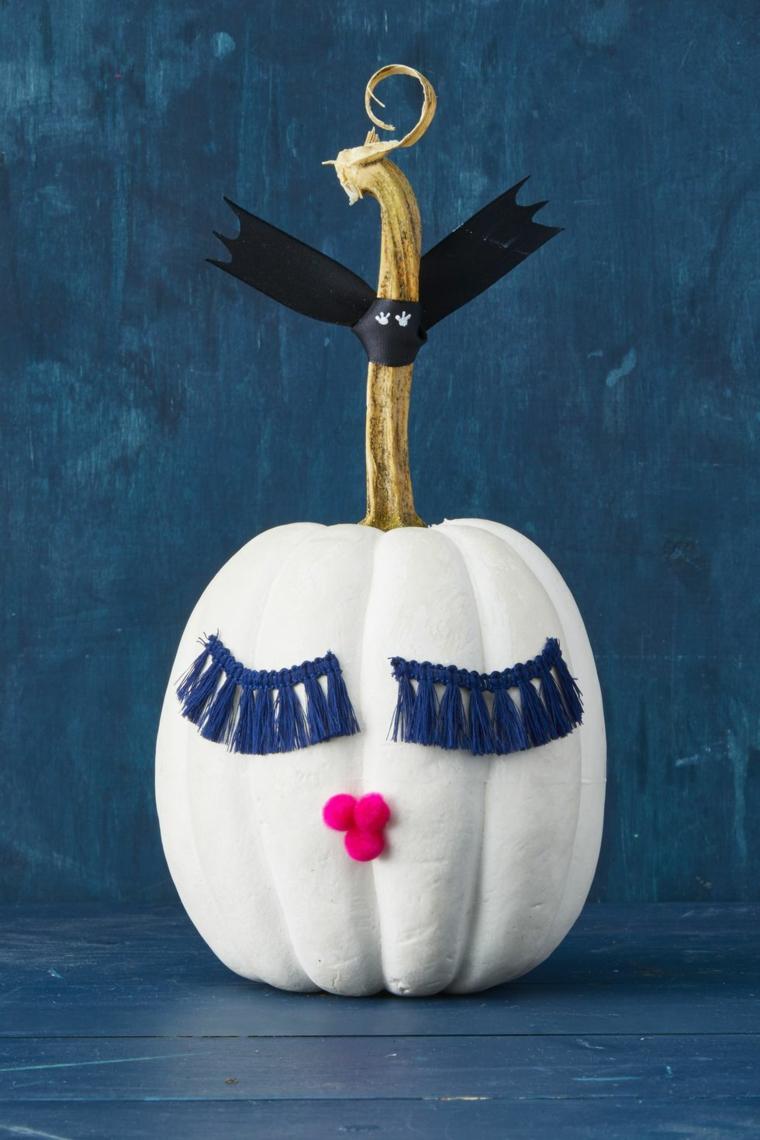 Zucca decorata con frange, zucca con pom pom, immagine sfondo colore blu