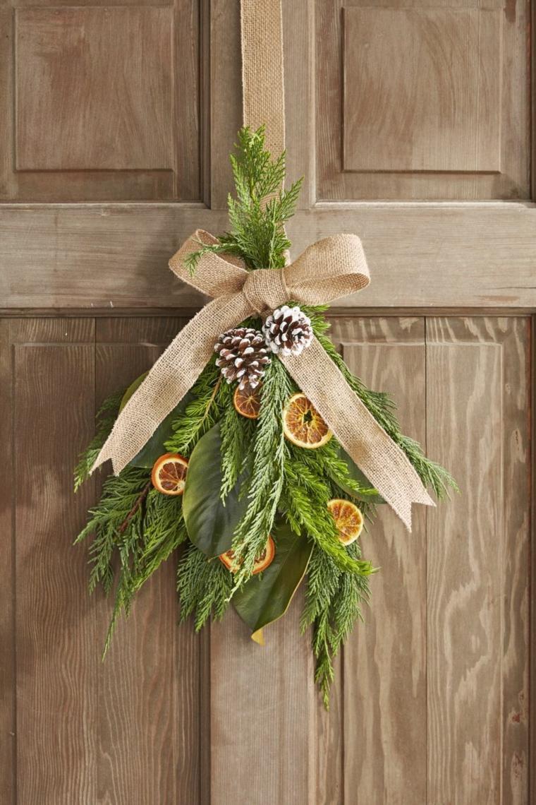 Decorazioni natalizie fai da te, decorazione della porta, bouquet di rametti di pino con pigne