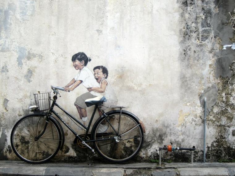 muro griggio facciata abbellito dipinto due bimbe bici