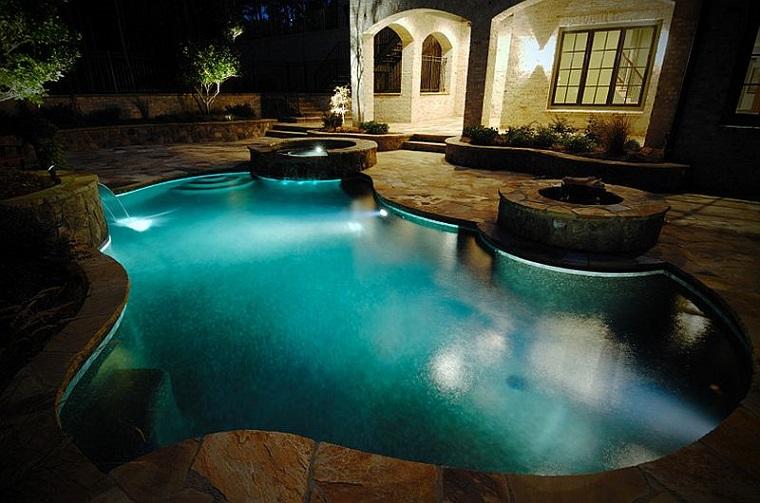 piscina forma irregolare luci notturni atmosfera elegante