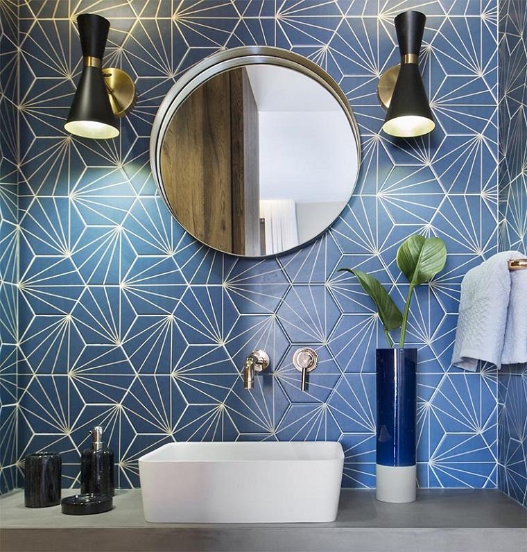 Piastrelle adatte ad un bagno piccolo, parete rivestita con piastrelle blu, specchio rotondo e due lampade