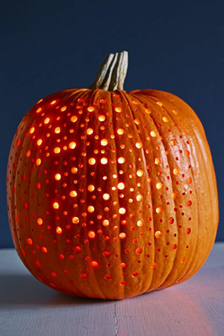 Zucche intagliate, zucca con piccoli buchi, decorazioni per Halloween con zucche lanterna