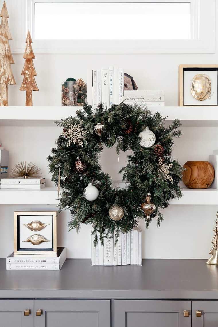Decori natalizi, corona di Natale con rametti verdi e pallina, soggiorno con mensole di legno