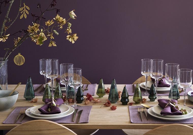 Addobbi natalizi fatti a mano, tavola apparecchiata con piatti e calici, vaso con rami e fogli secche