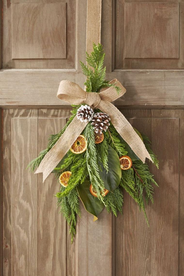 Decorazioni di Natale con rametti verdi, decorazioni natale porta d'ingresso, rametti con agrumi secchi