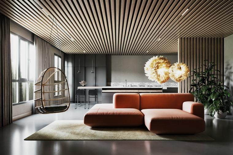 Divano di colore salmone, soffitto con travi di legno, open space con cucina, salotto moderno
