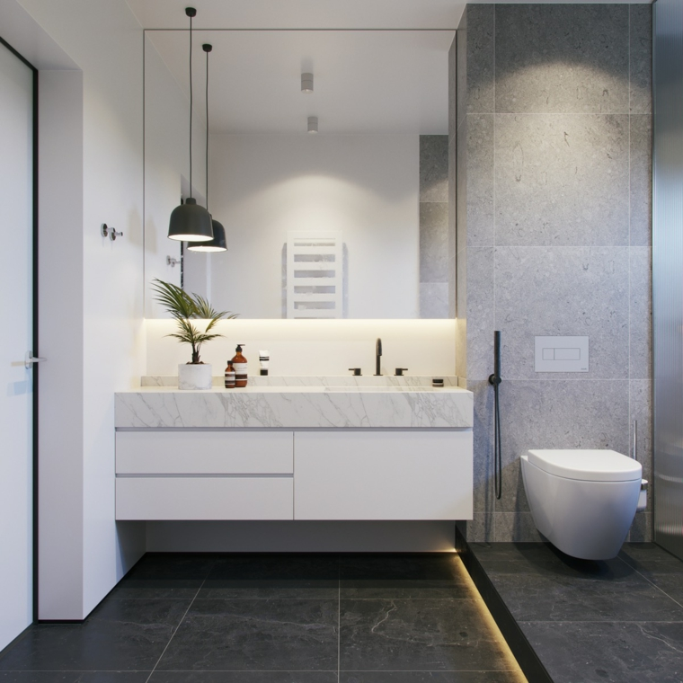 Sala da bagno con illuminazione soffusa, lavabo con superficie in marmo, decorazione con pianta