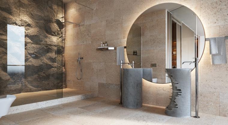 Piastrelle bagni moderni, parete effetto pietra a vista, specchio rotondo con retro illuminazione