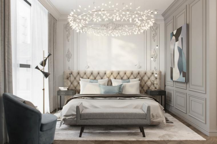 Lampadario in cristallo, pareti in legno colore bianco crema, testata letto imbottita, arredare camera da letto piccola