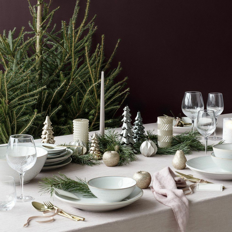 Tavola apparecchiata per Natale, centrotavola con rametti verdi, alberi di Natale 2019 tendenze