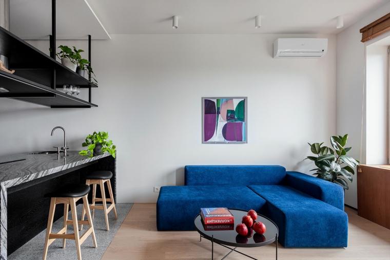 Un divano angolare di colore blu, un tavolino basso e rotondo, arredamento casa moderno