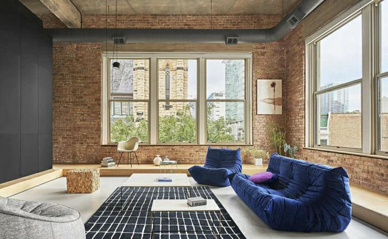 Pareti colorate soggiorno esempi, pareti di colore blu con mattoni, divano in tessuto blu