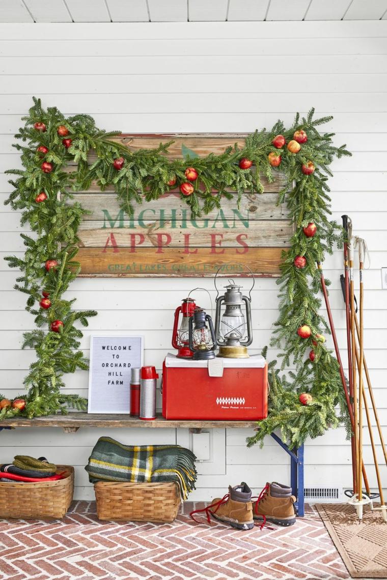 Ghirlanda natalizia con rametti e mele, panchina di legno, decorazioni di Natale fai da te
