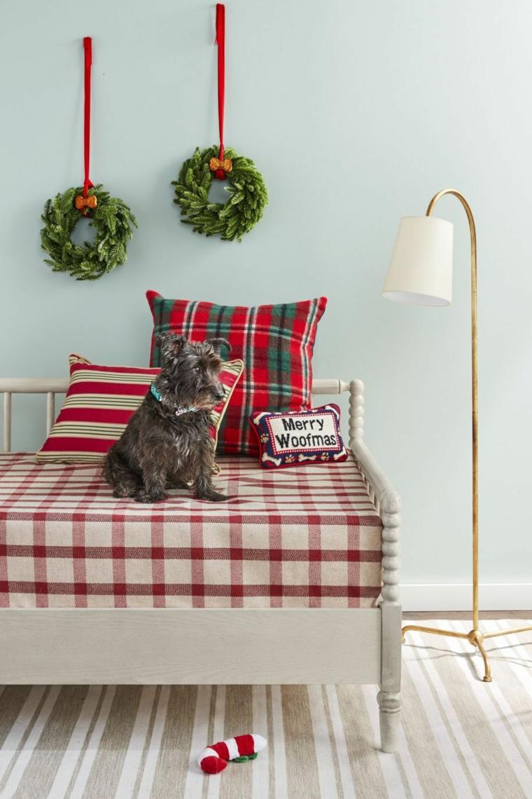 Cane sul divano, corone di rametti verdi, decorazione da parete con nastro e ghirlanda natalizia