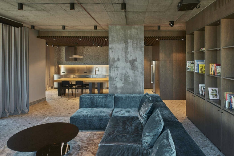 Un divano velvet blu, soffitto con faretti, cucina con isola centrale, salotto moderno