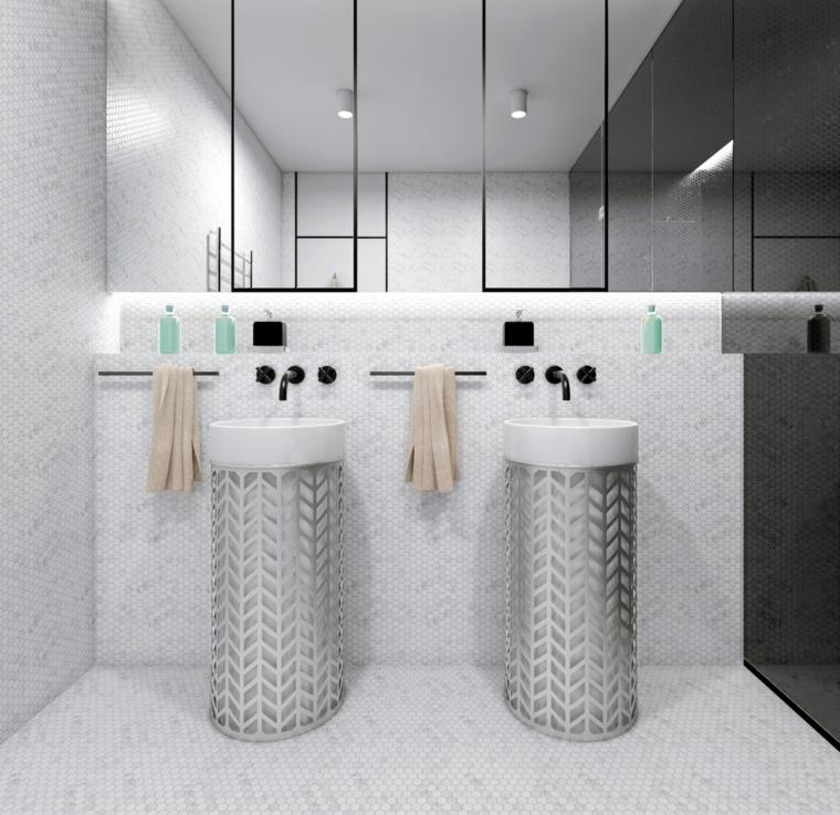 Sala da bagno con piastrelle mosaico, arredo con lavabi colonna, faretti sul soffitto