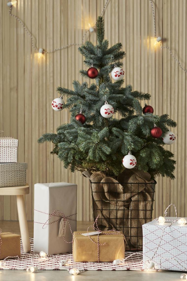 Pacchi regalo sotto l'albero, palline natalizie di colore rosso e bianco, alberi di Natale addobbati 2019