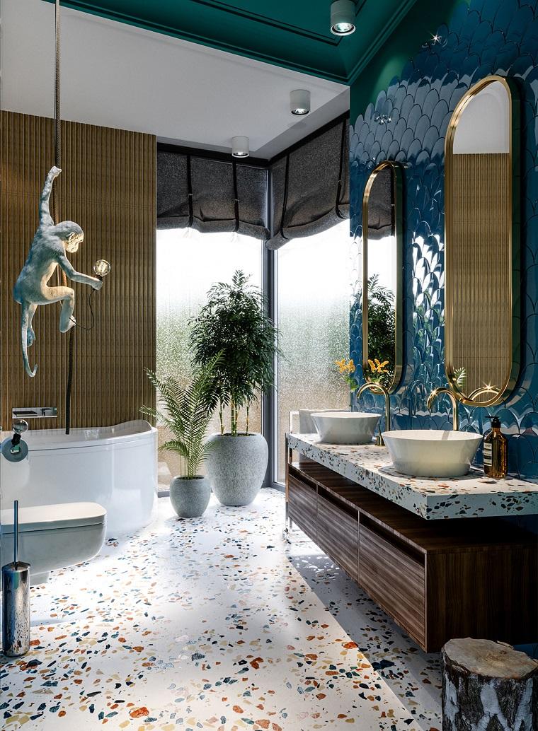 Bagno con pavimento in marmo, parete con piastrelle blu, mobile bagno con lavabo appoggio