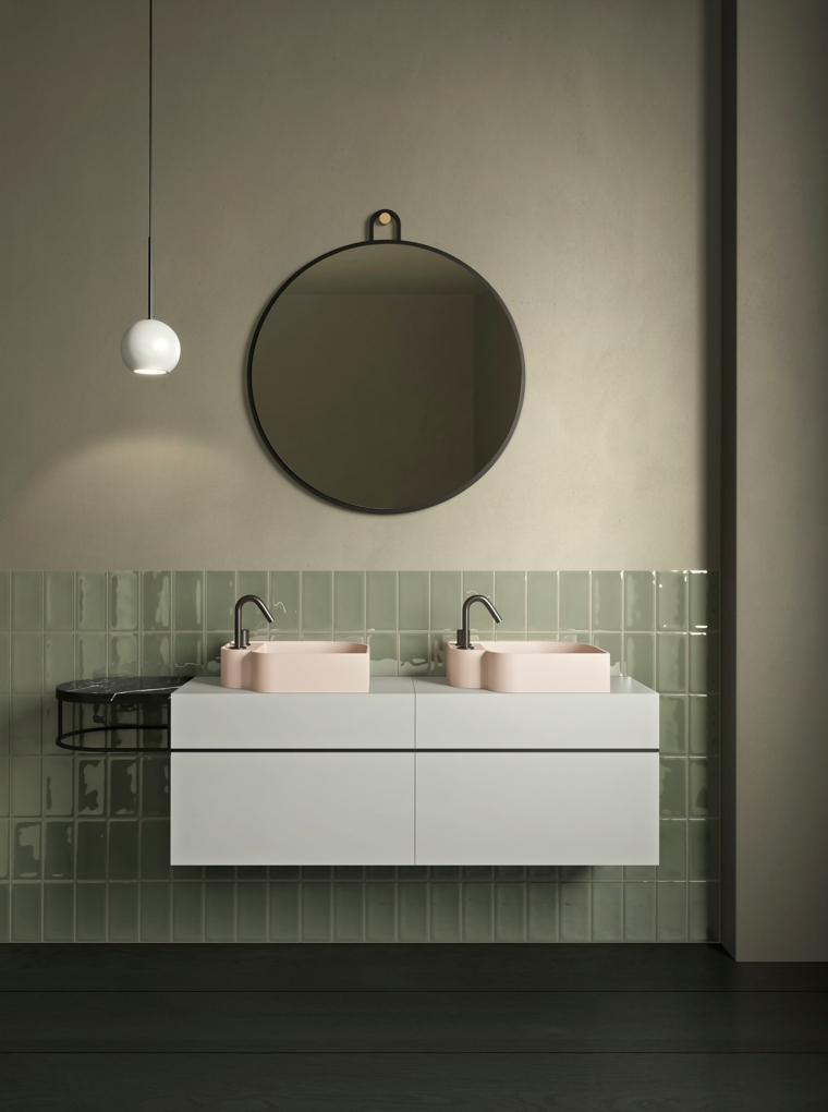 Bagno con mobile sospeso, due lavabi rosa, specchio rotondo, pavimento in legno