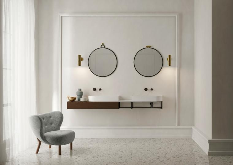 Bagno con mobile sospeso, due specchi da parete, lavabo da appoggio, poltrona in bagno