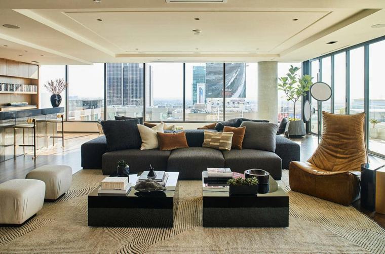 Open space con divano grigio, soggiorno con due tavolini bassi, soffitto con faretti