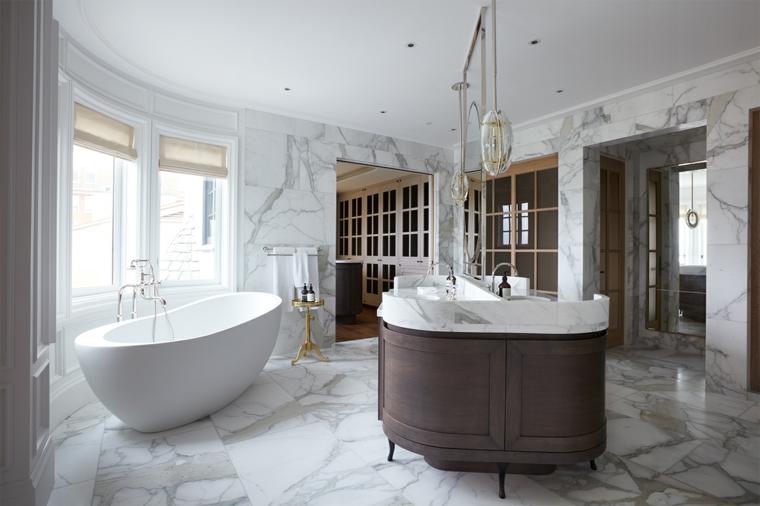 Vasca freestanding, pavimento bagno in marmo, lampade sospesi a dei fili