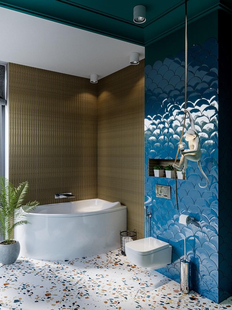 Bagni lussuosi, parete rivestita con piastrelle blu, vasca da bagno ad angolo