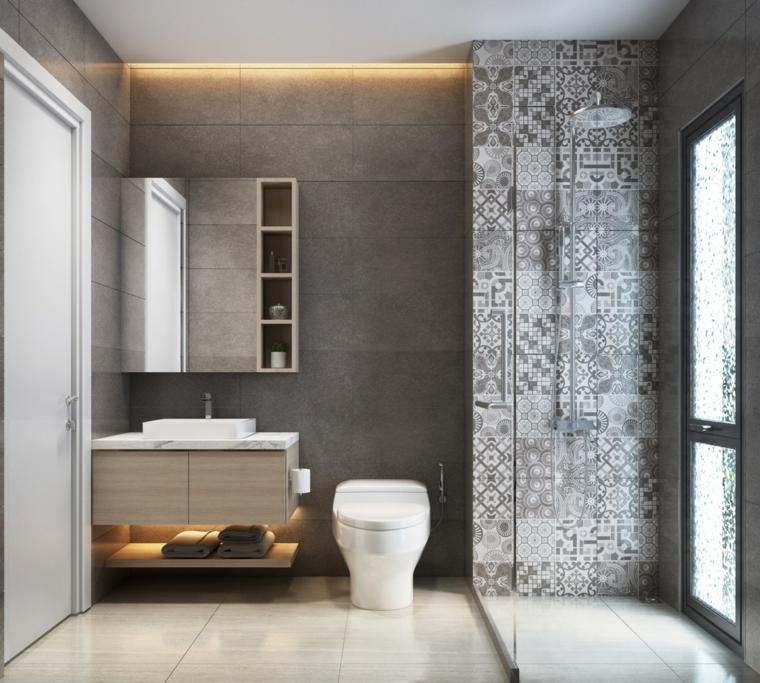 Sala da bagno con box doccia, mobile lavabo da appoggio, piastrelle pareti grigie, illuminazione nascosta