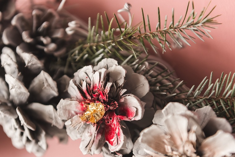 Pigne dipinte di colore grigio, ghirlanda natalizia con rametti e pigne, decori natalizi