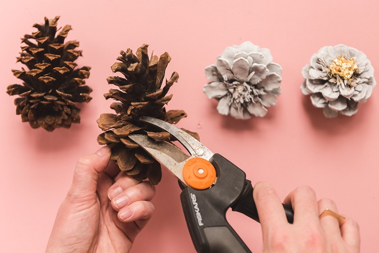 Tagliare le pigne con pinze, pigne dipinte di colore grigio, addobbi natalizi fai da te 2019