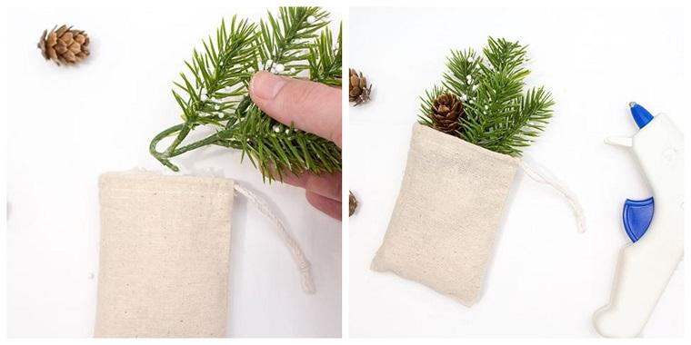 Sacchettino di stoffa con rametti verdi, pistola per colla a caldo, addobbi natalizi fatti a mano
