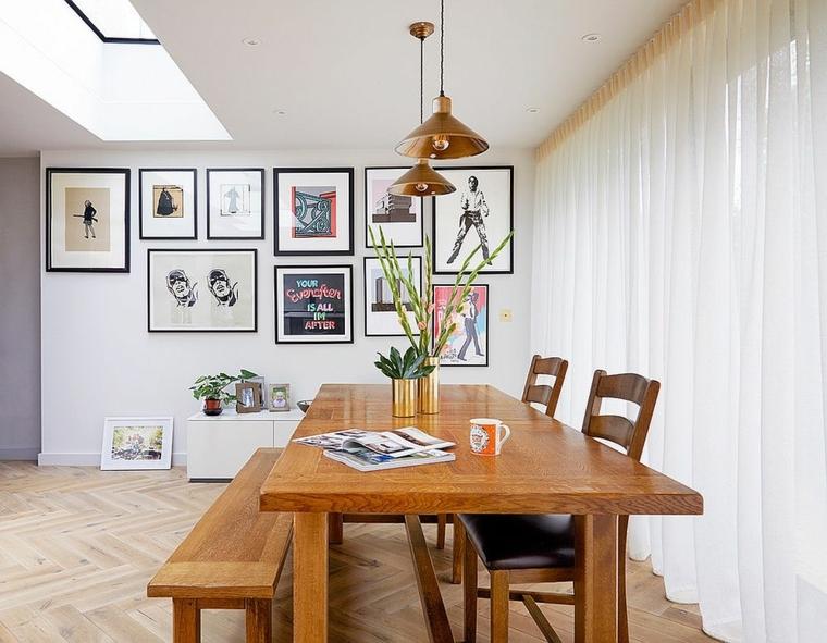 sala da pranzo con tavolo di legno con panchina parete bianca decorata con cornici