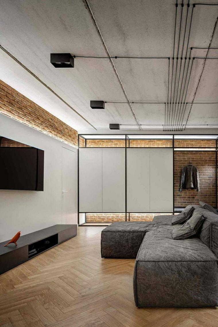 Idee pittura pareti soggiorno, divano angolare di colore grigio, pareti con mattoni a vista
