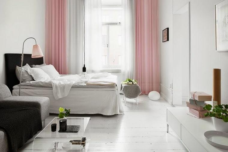 Arredare camera da letto piccola, tende di colore rosa, testata letto in tessuto nero, divano e tavolino