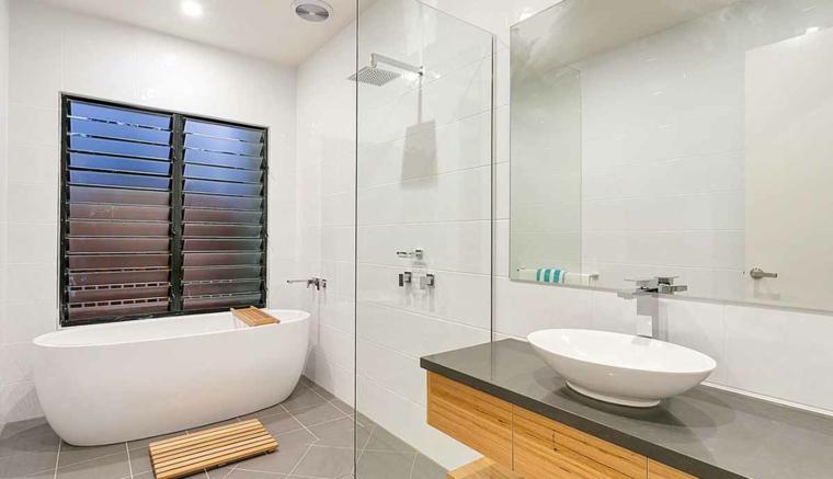 Vasca da bagno con bordi arrotondati, mobile di legno sospeso, lavabo da appoggio