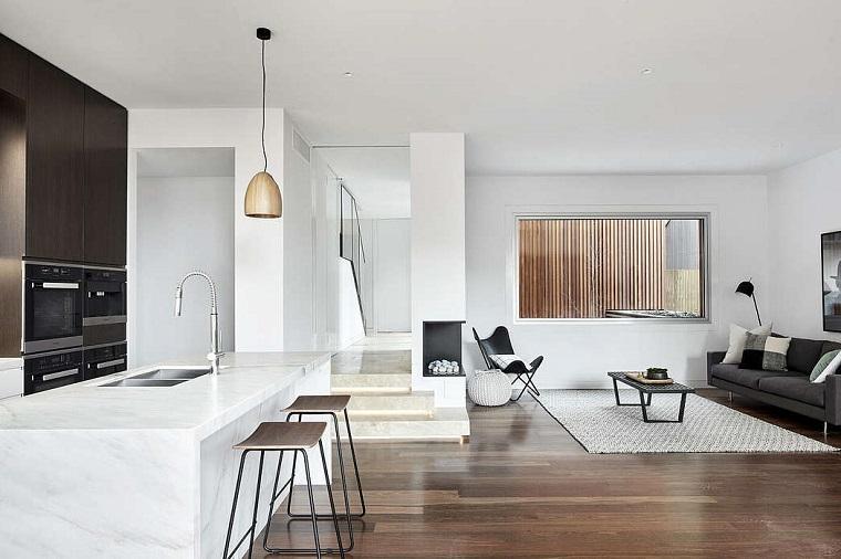 Isola centrale in marmo, soggiorno con divano grigio, pavimento in legno, soluzioni per dividere soggiorno e cucina