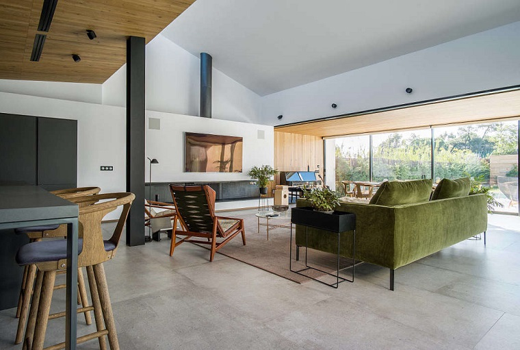 Come arredare sala e salotto insieme, tv appesa alla parete, divano in tessuto verde, pavimento gres porcellanato grigio