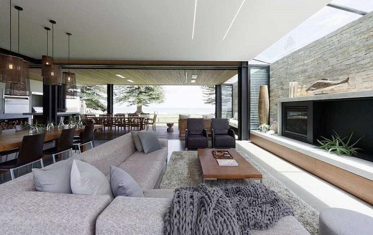 Loft significato, soggiorno con divano grigio, tavolo da pranzo in legno, parete effetto pietra