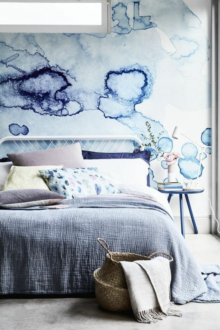 camera matrimoniale letto parete dipinta como tavolino cesto cuscini coperte