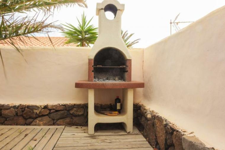 Giardino con parete bianca e barbecue, costruire barbecue in muratura
