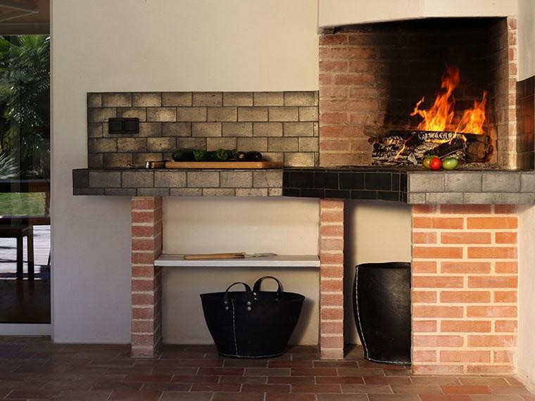 Cucina esterna con barbecue a legna, barbecue con piano di lavoro in mattoni e piastrelle