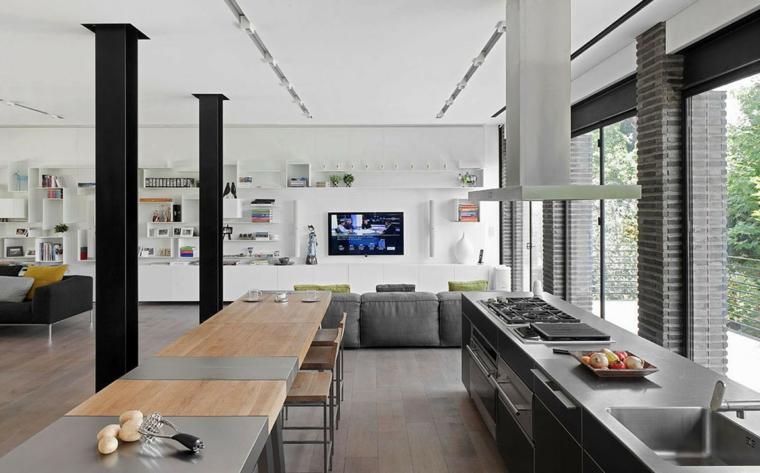 Divano colore grigio, cucina con isola centrale, soggiorno con mensole, living con finestre